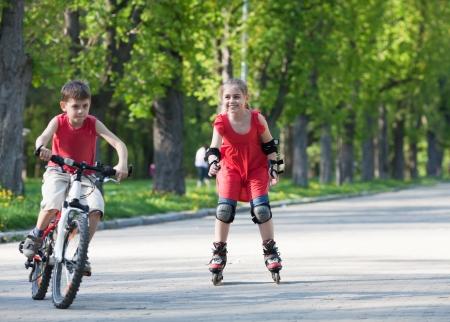 Belle petite fille sur patins à roues alignées souriant et en regardant petit garçon à vélo en face de son