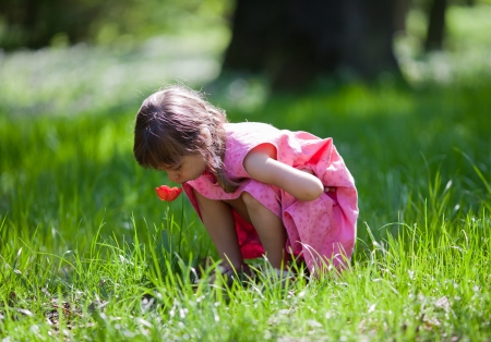 Beautiful little girl in pink dress sitting and sniffing tulip in the park
