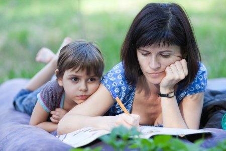 Mum doing crossword, daughter lies next to her mother, outdoors  photo