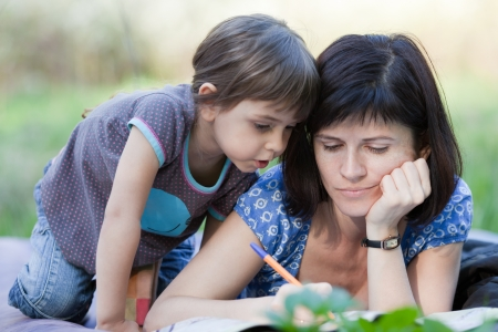Mother doing crossword, little daughter looks at it Stock Photo - 13894228