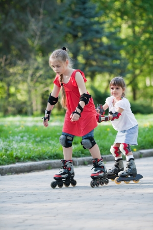 Beautiful little girls on rollerblades in a park  Older gilr helps her younger sister skating Фото со стока