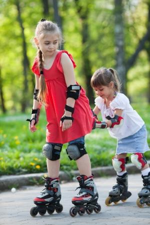 Belles petites filles sur le cyclisme en ligne patins dans un parc Banque d'images
