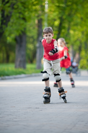 Little boy and girl in background rollerblade in park Фото со стока