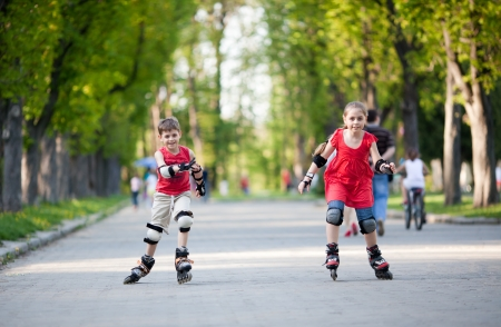 Little boy and girl on rollerblades competing photo