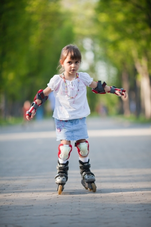 Adorable little girl gains confidence on rollerblades photo