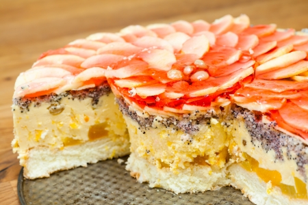 luscious: Closeup of  sliced cheesecake topped with luscious apple slices and raisins in a red jelly  Few slices missing