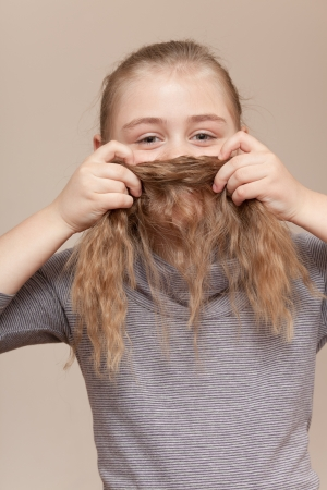 Little girl is making a moustache from her hair for fun photo