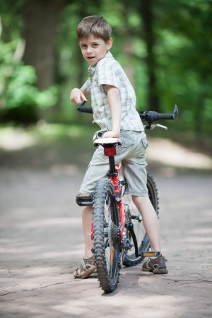 looking over shoulder: Eight years old caucasian boy on his bike at sunny day in the park  Looking over his shoulder Stock Photo