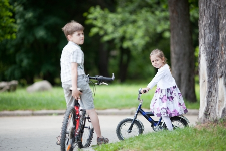 Girl, 4 years, and boy, 8 years, riding bicycles in the park. photo