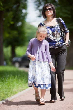 Mother and daughter walking in the summer park photo