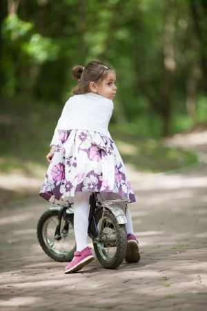 Four years old caucasian girl on her bike at sunny day in the park. Looking over her shoulder photo