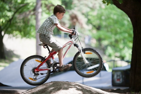 Mountain bike rider is jumping on his bicycle in a park photo