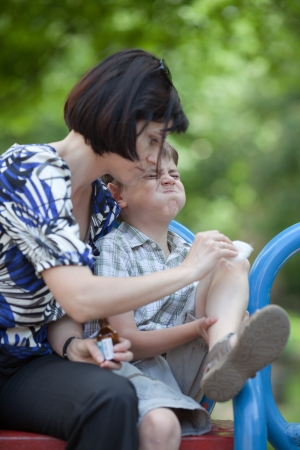 wound care: Mum helping her son who scraped his knee Stock Photo