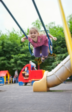 Little girl swinging on the playground at summer day