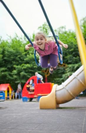 Petite fille balançant sur le terrain de jeu de jour d'été