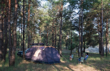 Camping at pine forest  Black tent, car with equipment  Family resting outdoors photo