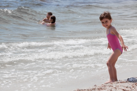 Little girl near the sea and two kids swimming photo