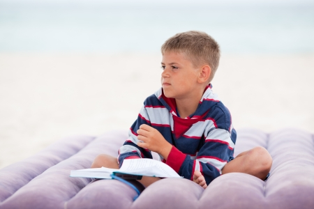 Pensive boy sitting on mattress with book photo