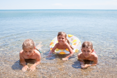 Three children have the water-based recreation on Black sea, Crimea, Ukraine photo