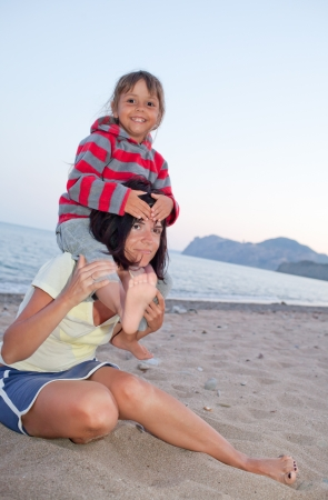 Mother and daughter playing in the beach, carrying on shoulders Stock Photo