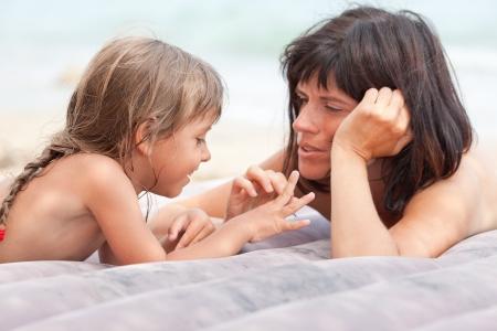 ni�os hablando: Madre e hija acostada en el colch�n, jugar y relajarse en la playa
