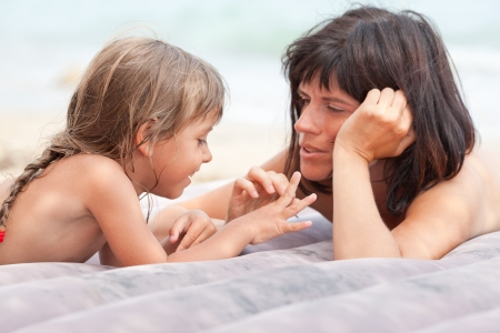 Mother and daughter  lying on mattress, playing and relaxing on the beach