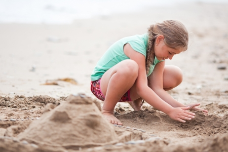 Girl playing at the beach, building castle of sand