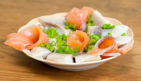 Fresh herring cut-out and rollmops of salmon fish decorated with green onion photo