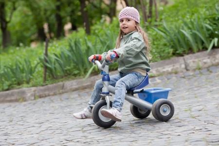 4 années vieux jean fille portant chapeau rose, et des promenades en manteau vert sur un tricycle