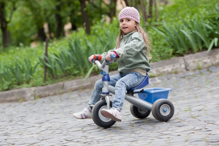 playful behaviour: 4 years old girl wearing jeans, pink cap and green coat rides on tricycle
