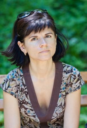 Femme adulte assis sur un banc, portrait Banque d'images