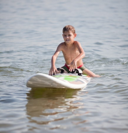 Young boy practicing surfing moves on windsurfing board on water photo