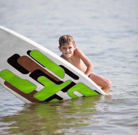 Young boy practicing surfing moves on windsurfing board on water
