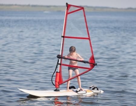windsurfing: Little boy go windsurfing Stock Photo