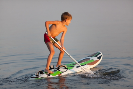 Little boy standing on  the windsurfing board with paddle  Evening light Фото со стока