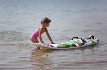 Little girl exploring windsurfing board photo