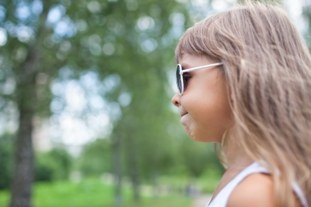 sidewards: little girl with sunglasses is looking sidewards