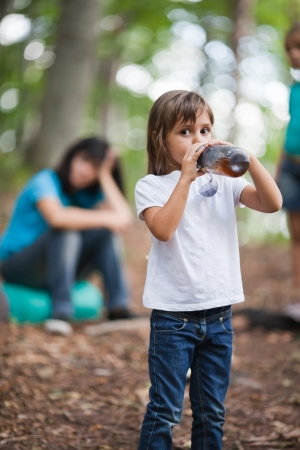 Little girl hiker drinks a cold tea from bottle while resting  Family on background photo
