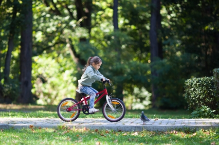 Little girl riding red bike in fall park