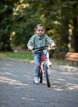 Little girl riding red bike in fall park  photo
