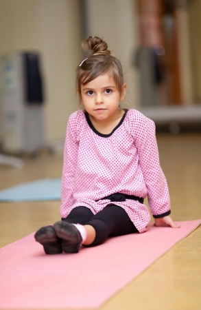 6 years: 5 year old little girl doing sports exercises on the mat Stock Photo