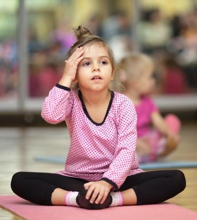 Fille de 5 ans peu assis sur la natte à dacing leçon