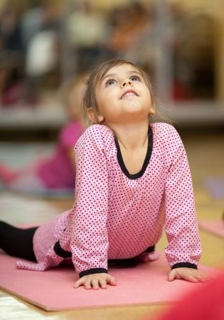 niños bailando: Niña de 5 años que hace ejercicios deportivos en la estera estiramiento