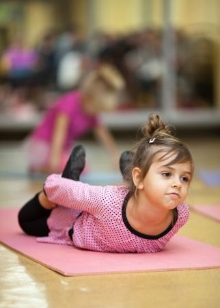 5 ans petite fille faisant des exercices de sport sur le tapis d'étirement