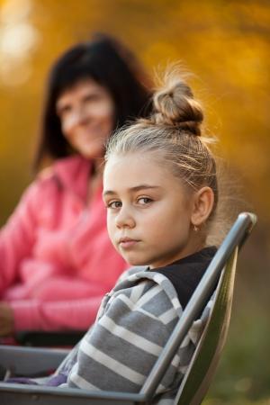 Portrait de jolie jeune fille avec sa mère en arrière-plan