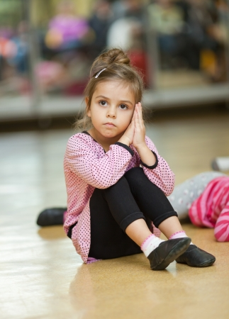 aerobic exercise: 5 year old little girl doing dance exercises on the floor Stock Photo