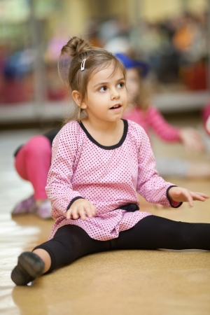 5 year old little girl doing dance exercises on the floor photo