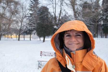 Portrait of a smiling woman in orange jacket with hood photo
