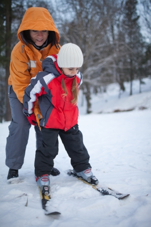 Mother coaching her young daughter downhill skiing