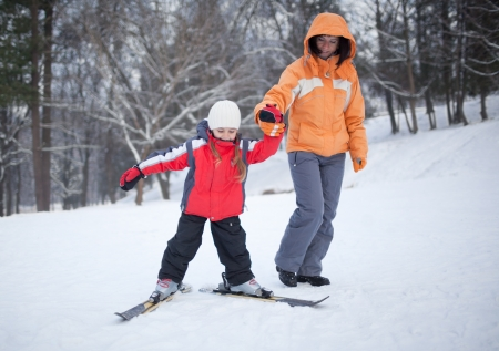 Mother coaching her young daughter downhill skiing photo